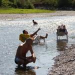 """Italai kaimiečiai deginasi upėje """"Olio""""."""